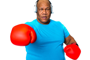 older black man boxing with boxing gloves and listens to music in his headphones