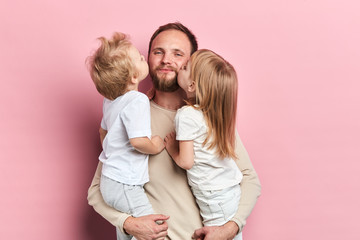 little daughter and son kissing their father isolated over a pink background, close up portrait,...
