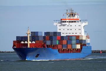 blaues Feederschiff kommt im Hafen an