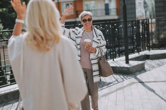 Woman waving goodbye to her cheerful friend