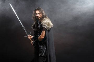 Man dressed in medieval armor and raincoat with longs word over smoke background. Courage fantasy warrior knight with long hair concept historical photo