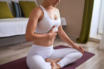 Close-up of woman sitting on exercise purple mat in lotus position while eyes closed and breathtaking. Keep calm