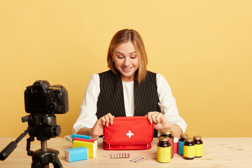 Happy blonde lifestyle blogger looks inside of first-aid bag with joyful expression, enjoys her hobby, gets ready to start broadcasting new content at personal account in social network.