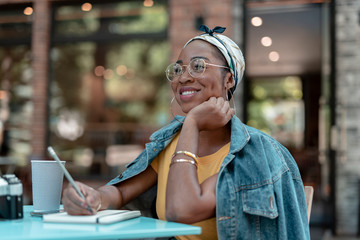 Happy woman with sketchbook drinking coffee outdoors stock photo