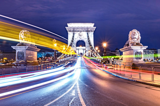The Chain Bridge in Budapest at night. Moving lights of the cars.