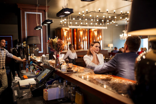 Attractive good shaped woman dressed in white clothes, touching neck thoughtfully sitting at bar counter together with handsome friend at restaurant, side view