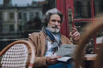 Frowning man with cigar and newspaper at the table stock photo