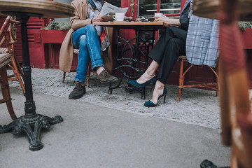 Elegantly dressed couple sitting at the cafe table stock photo