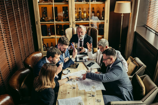 Team of specialists happily concluded important meeting. Young coworkers closed eyes with relief, raised hands in the air, Old man at the head of conference table raised a glass of whiskey