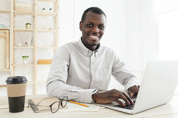 Smiling african american worker using his laptop in white office