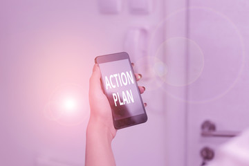Word writing text Action Plan. Business photo showcasing detailed plan outlining actions needed to reach goals or vision woman using smartphone office supplies technological devices inside home