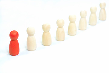 Leadership concept. Red wooden figurine leading the other wooden figurines.