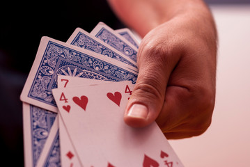 A hand holding poker cards