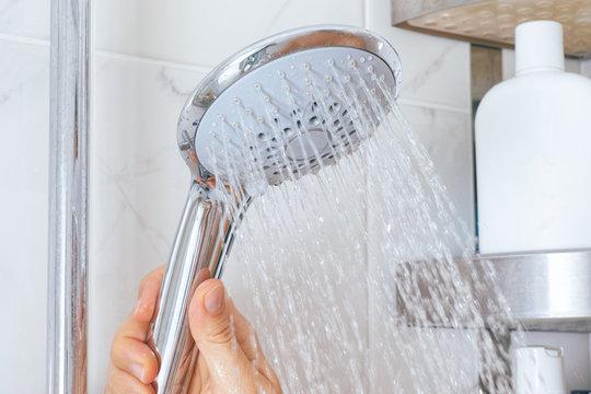 Woman hand using shower head in bathroom.