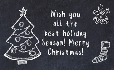 Drawing of christmas tree and handwritten greetings on black chalkboard