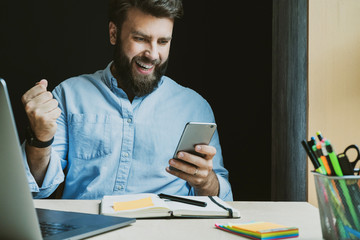Obraz Man rejoices in victory while looking at screen of smartphone. Worker at desk with laptop and notebook. Male getting high-paid job - fototapety do salonu