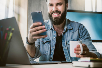 Manager having break in office, communicating with online friend in social network on smartphone. Smiling man watching funny video
