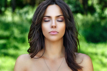 Beautiful woman face with perfect skin and eyes closed. Close up portrait on nature background