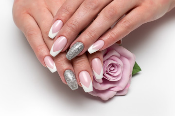 Aluminium Prints Manicure Wedding sharp French manicure with silver sequins on the ring fingers on a white background close-up on long nails with a pink rose in hand