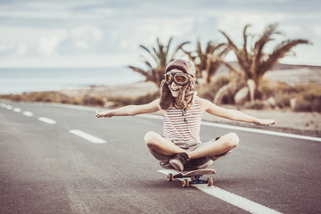 Young blond boy plays aviator sitting cross-legged on skateboard with arms outstretched to fly smiling child imitates plane flying on airport runway. Concept image of a plane taking off for a vacation