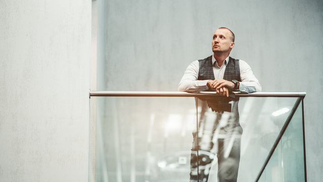 An adult caucasian pensive man entrepreneur is leaning on the chromium fence of a glass balcony in modern office settings, with a copy space place on the left for your logo or a text message