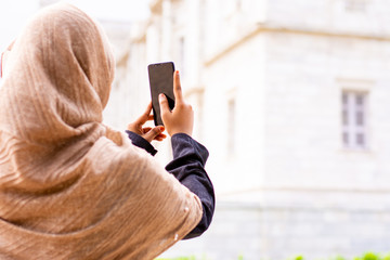 Young Burnett Muslim women wearing hijab and taking selfie or clicking photos with smartphone in park