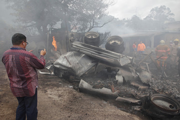 A reporter takes a picture of the wreckage of a fuel tanker that overturned and caught fire damaging infrastructure, vehicles and houses, in Tegucigalpa