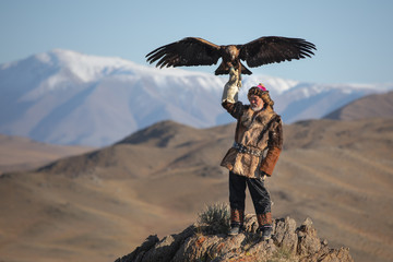 Old traditional kazakh eagle hunter posing with his golden eagle in the mountains. Ulgii, Western Mongolia.