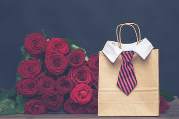 Concept of a gift for the day of lovers from a man.  large armful of red roses and a gift bag with a men's tie.