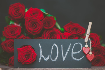 Concept Valentine day, the word love written in chalk on a plate on a background of a pile of red roses. Stylish love concept
