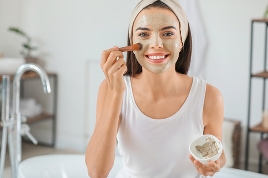 Beautiful young woman applying facial mask at home
