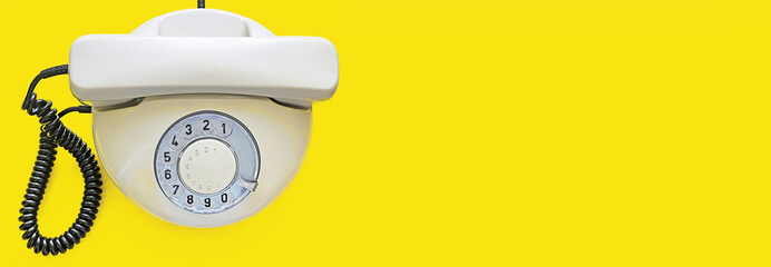 Biege old telephone with rotary dial on yellow background. Flat lay. Top view. Banner. Place for text