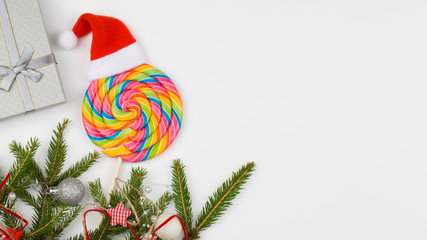 Christmas gift, Colorful lollipop and Fir Tree branches on white background. Holiday concept.
