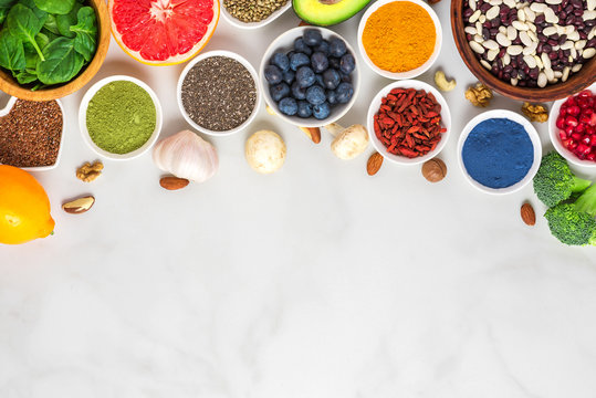 Healthy vegan food clean eating selection: fruit, vegetable, seeds, superfood, nuts, berries on white marble background