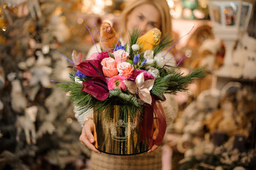 Girl holding a golden box of pink roses and crimson calla lilies decorated with pine branches and two parrots