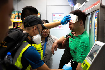 A man receives help by rescue workers after he was hit by anti-govenrment protesters during a protest at Tseung Kwan O district, in Hong Kong