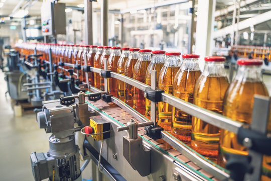 Conveyor belt, juice in glass bottles on beverage plant or factory interior, industrial manufacturing production line