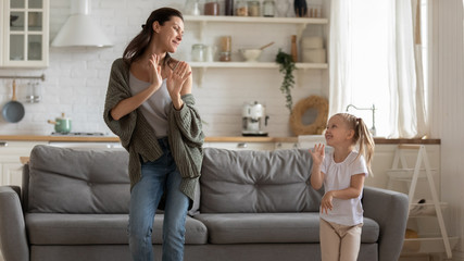 Happy mother and cute little daughter dancing in living room