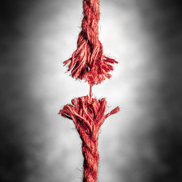 Frayed Red Rope Hanging By Last Thread On Black And White Background