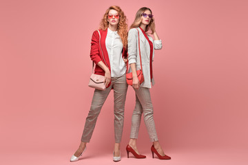 Two fashionable woman sisters in Trendy autumn red elegant outfit, stylish hair, makeup hugging. Gorgeous friends in jacket, heels on pink. Sensual model girl, stylish pastel fashion accessories Wall mural