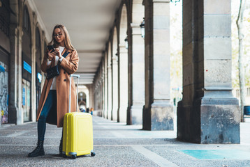Tourist with suitcase holding mobile phone. Girl travels in Barcelona. Holiday concept in Spain street. Traveler hipster in glasses using cellphone online technology in europe trip. Copy space mockup