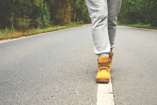 The girl goes along the line of road markings. Walk along the autumn road. Hipster Traveling, Lifestyle. White road markings and legs in autumn shoes.