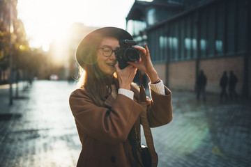 Outdoor smiling lifestyle portrait of pretty young woman having fun in sun city in Europe with camera travel photo of photographer Making pictures in hipster style glasses and hat