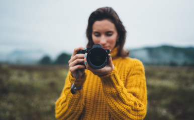 Wall Mural - photographer girl hold in hands video camera take photo on background autumn foggy mountain, tourist shooting nature mist landscape, hobby concept