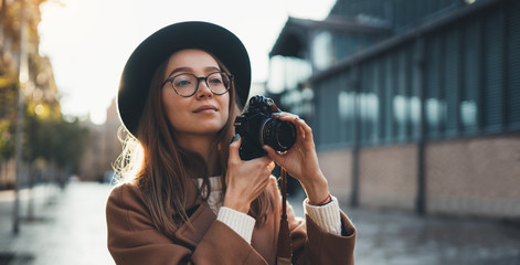 Hobby photographer concept. Outdoor lifestyle portrait of pretty woman in sun city in Europe with camera travel photo of photographer in glasses and hat take photo copy space mockup