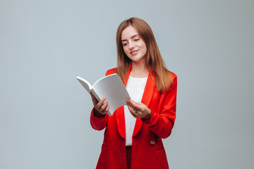 girl in a red jacket holds a presentation of the book on a gray background