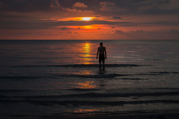 standing in the asian sea at sunset