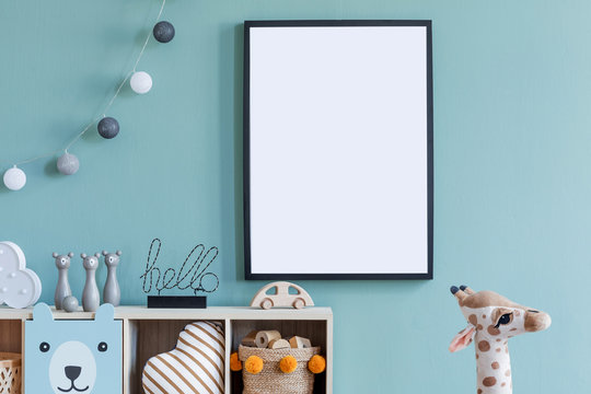 Stylish scandinavian newborn baby room with wooden cabinet, toys, mock up poster frame and children's accessories. Modern interior with eucalyptus background wall and cottona balls. Modern home decor.
