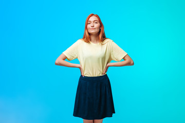 Red-haired girl in a short skirt stands on a blue-green background