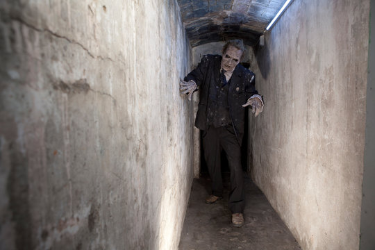 A zombie is walking towards us in a tunnel. Useful in halloween a horror events